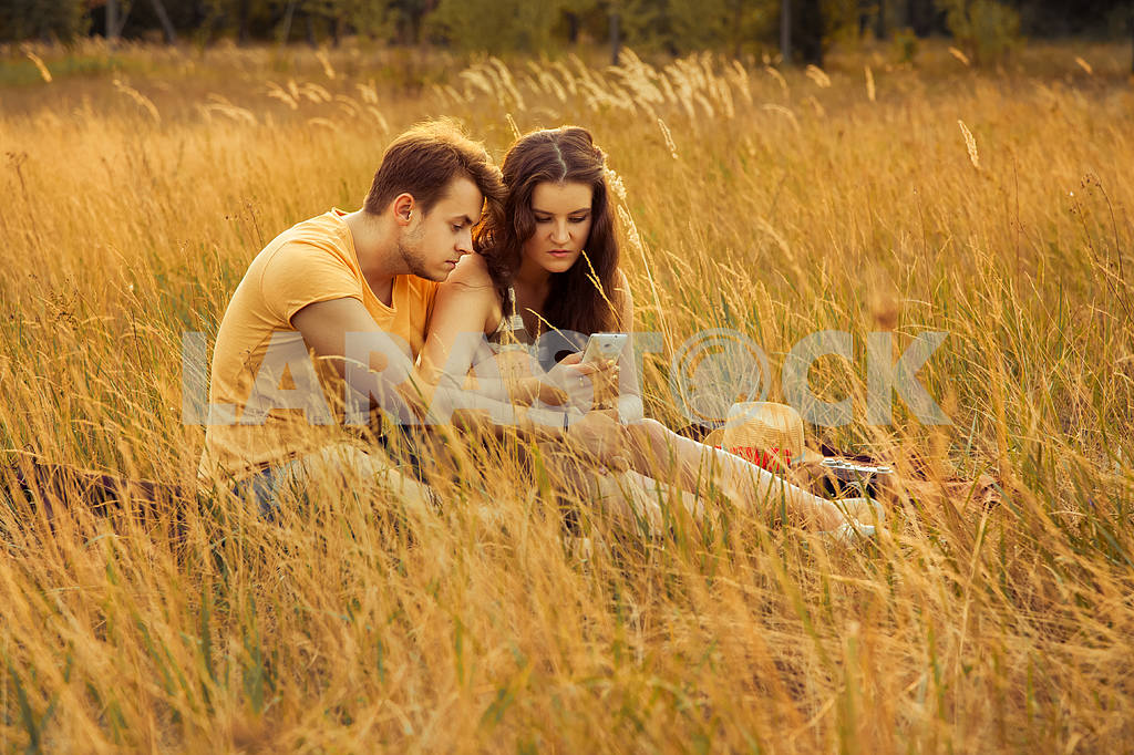 Young fashion beautiful loving casual style couple  lying down on floral field in autumnal park, warm sunny day, enjoying family, romantic date, happiness and love concept. — Image 19848