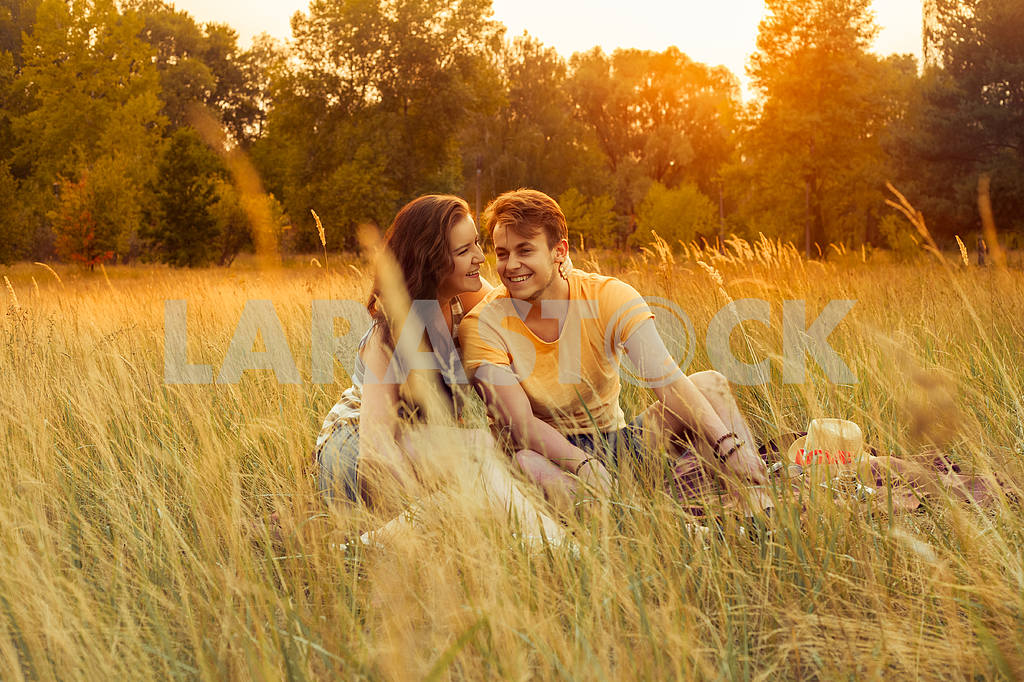 Young fashion beautiful loving casual style couple  lying down on floral field in autumnal park, warm sunny day, enjoying family, romantic date, happiness and love concept. — Image 19851