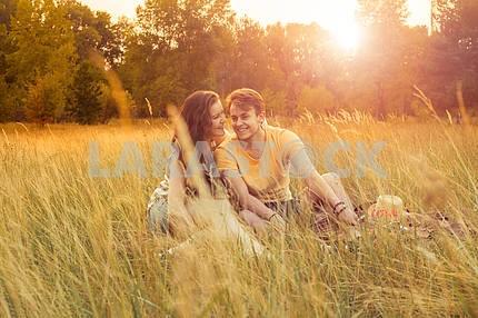 Молодой красивый любящей моды случайный стиль пара , лежа на цветочным области в осенний парк, теплый солнечный день , наслаждаясь семьи , романтическое свидание , счастья и любви концепции.