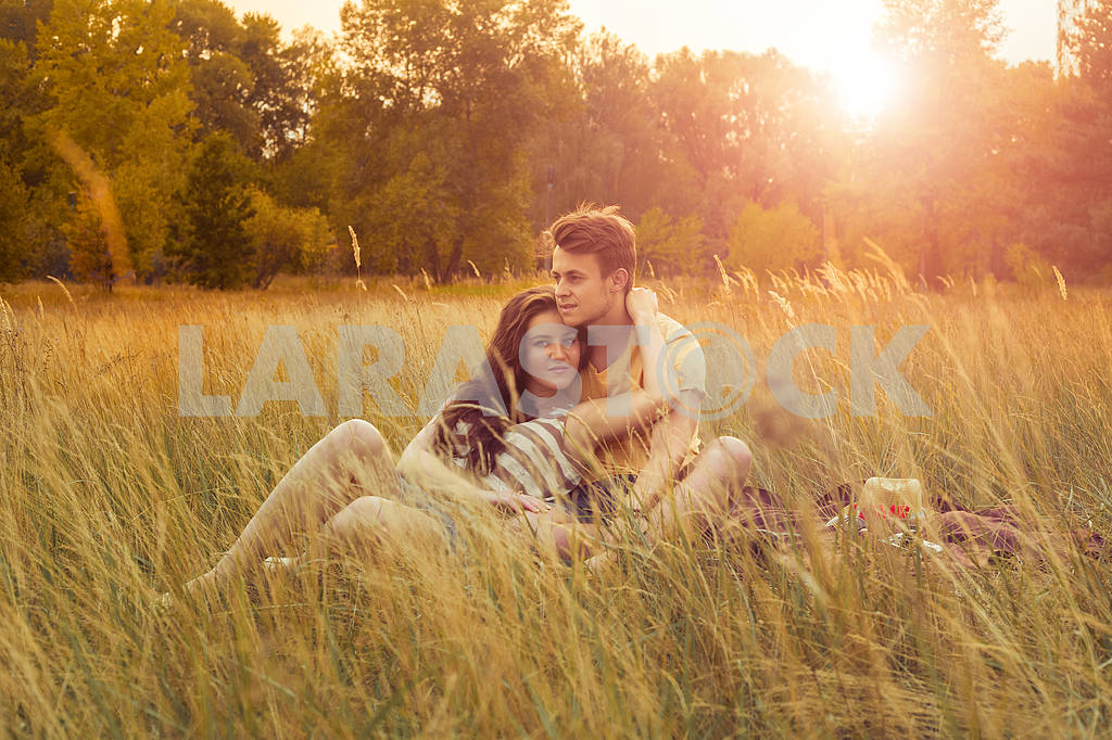 Young fashion beautiful loving casual style couple  lying down on floral field in autumnal park, warm sunny day, enjoying family, romantic date, happiness and love concept. — Image 19858