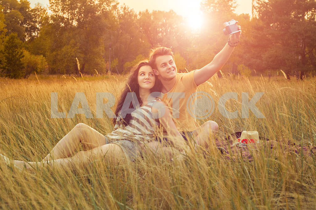 Young fashion beautiful loving casual style couple  lying down on floral field in autumnal park, warm sunny day, enjoying family, romantic date, happiness and love concept. — Image 19860