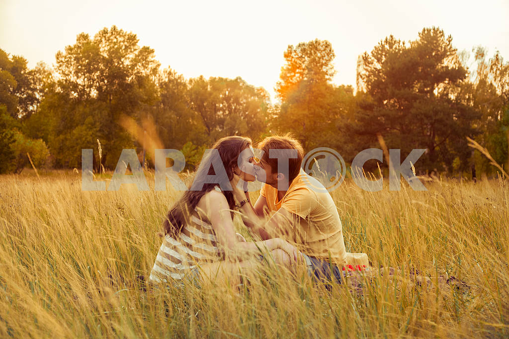 Young fashion beautiful loving casual style couple  lying down on floral field in autumnal park, warm sunny day, enjoying family, romantic date, happiness and love concept. — Image 19861