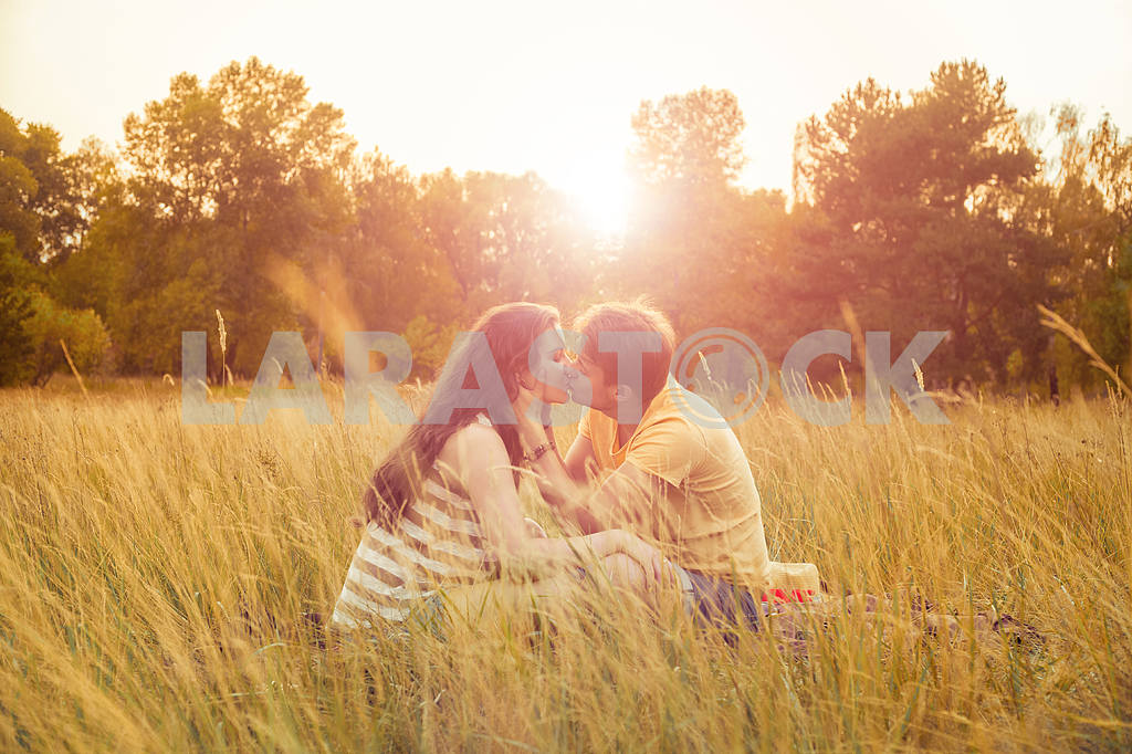 Young fashion beautiful loving casual style couple  lying down on floral field in autumnal park, warm sunny day, enjoying family, romantic date, happiness and love concept. — Image 19862