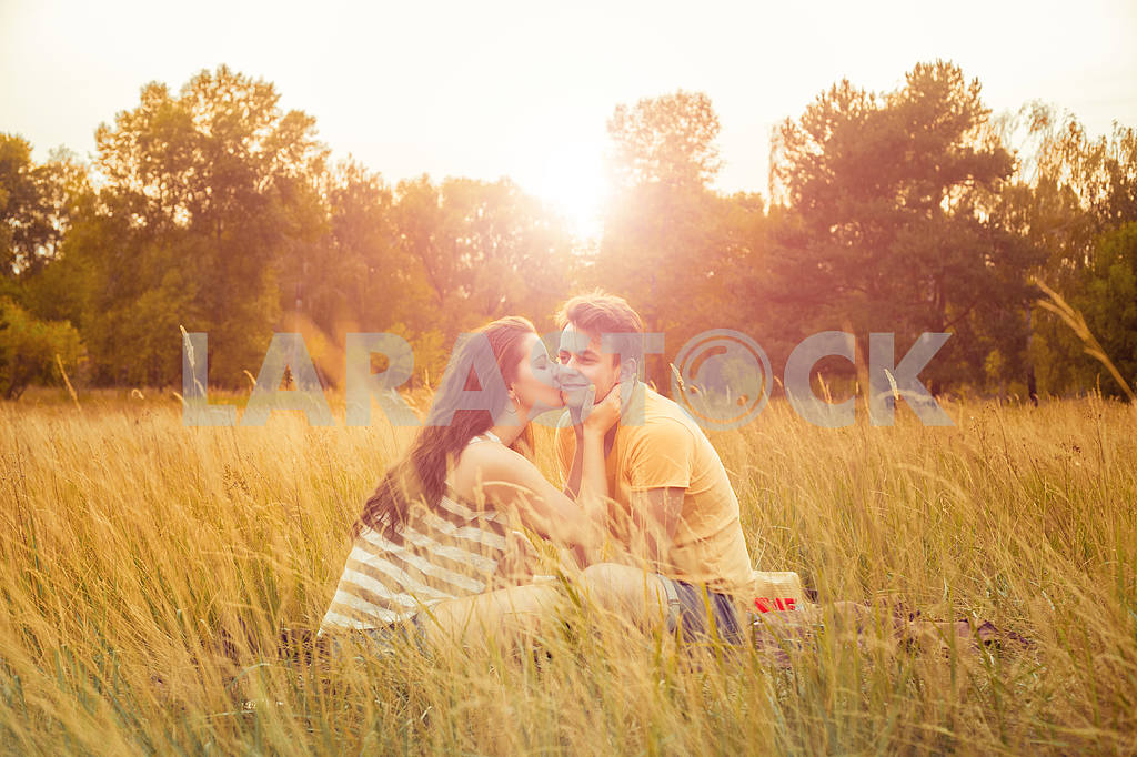 Young fashion beautiful loving casual style couple  lying down on floral field in autumnal park, warm sunny day, enjoying family, romantic date, happiness and love concept. — Image 19863