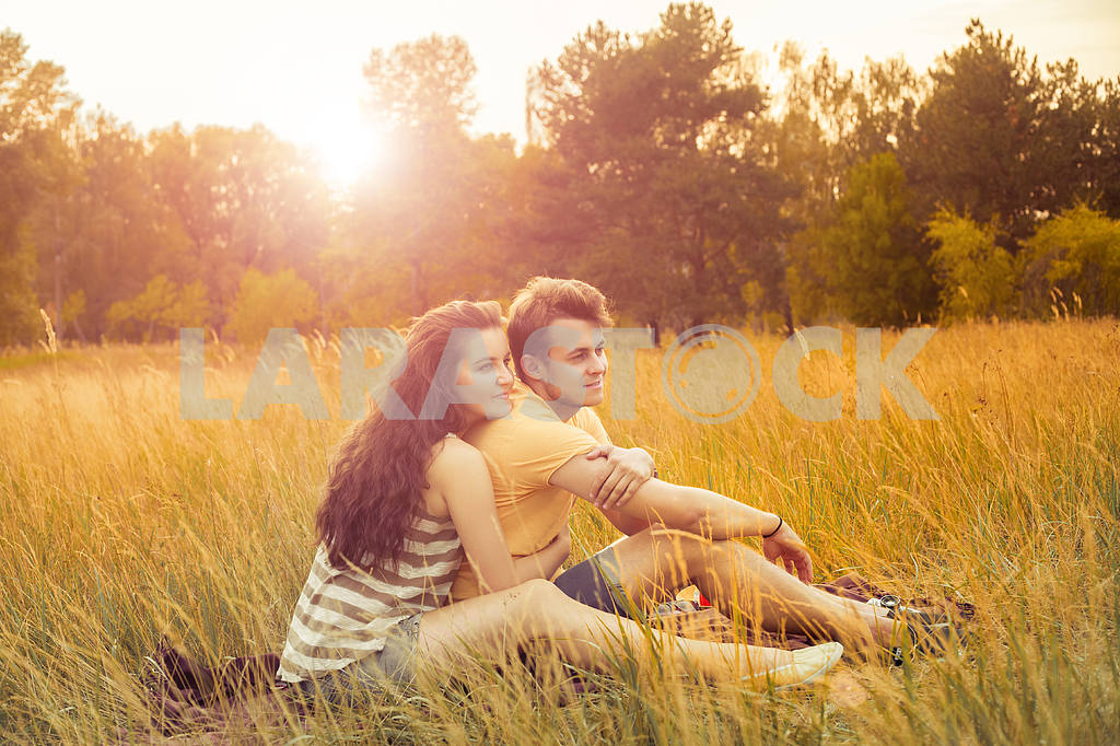 Young fashion beautiful loving casual style couple  lying down on floral field in autumnal park, warm sunny day, enjoying family, romantic date, happiness and love concept. — Image 19865