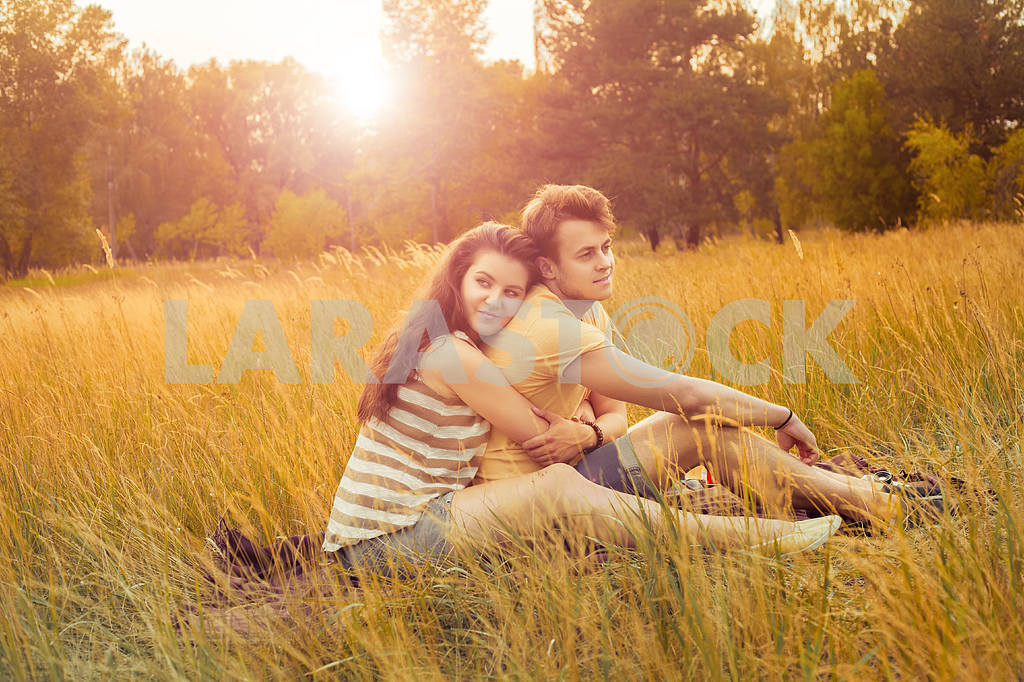 Young fashion beautiful loving casual style couple  lying down on floral field in autumnal park, warm sunny day, enjoying family, romantic date, happiness and love concept. — Image 19866