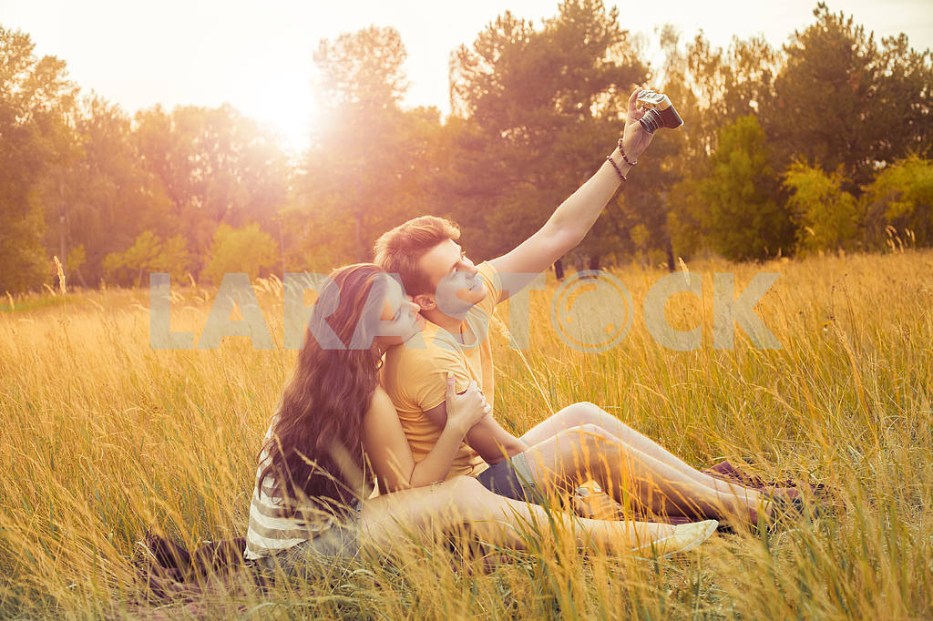 Young fashion beautiful loving casual style couple  lying down on floral field in autumnal park, warm sunny day, enjoying family, romantic date, happiness and love concept. — Image 19868