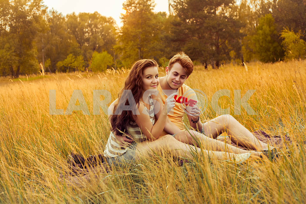 Young fashion beautiful loving casual style couple  lying down on floral field in autumnal park, warm sunny day, enjoying family, romantic date, happiness and love concept. — Image 19869