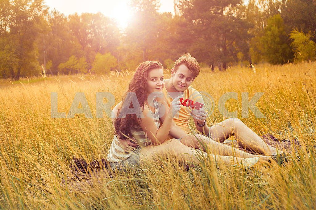 Young fashion beautiful loving casual style couple  lying down on floral field in autumnal park, warm sunny day, enjoying family, romantic date, happiness and love concept. — Image 19870