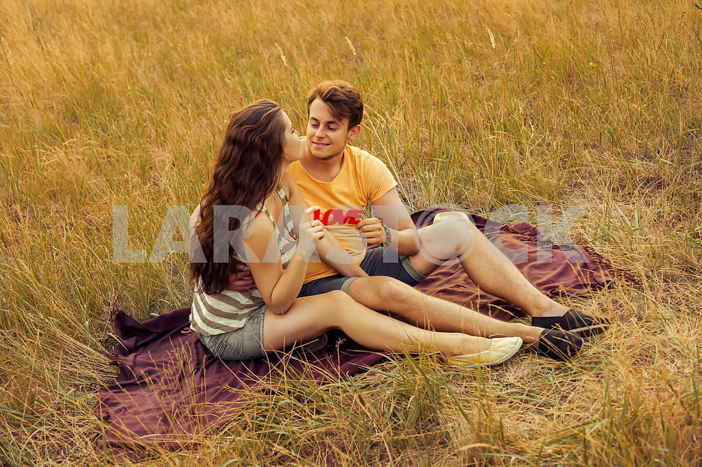 Young fashion beautiful loving casual style couple  lying down on floral field in autumnal park, warm sunny day, enjoying family, romantic date, happiness and love concept. — Image 19871