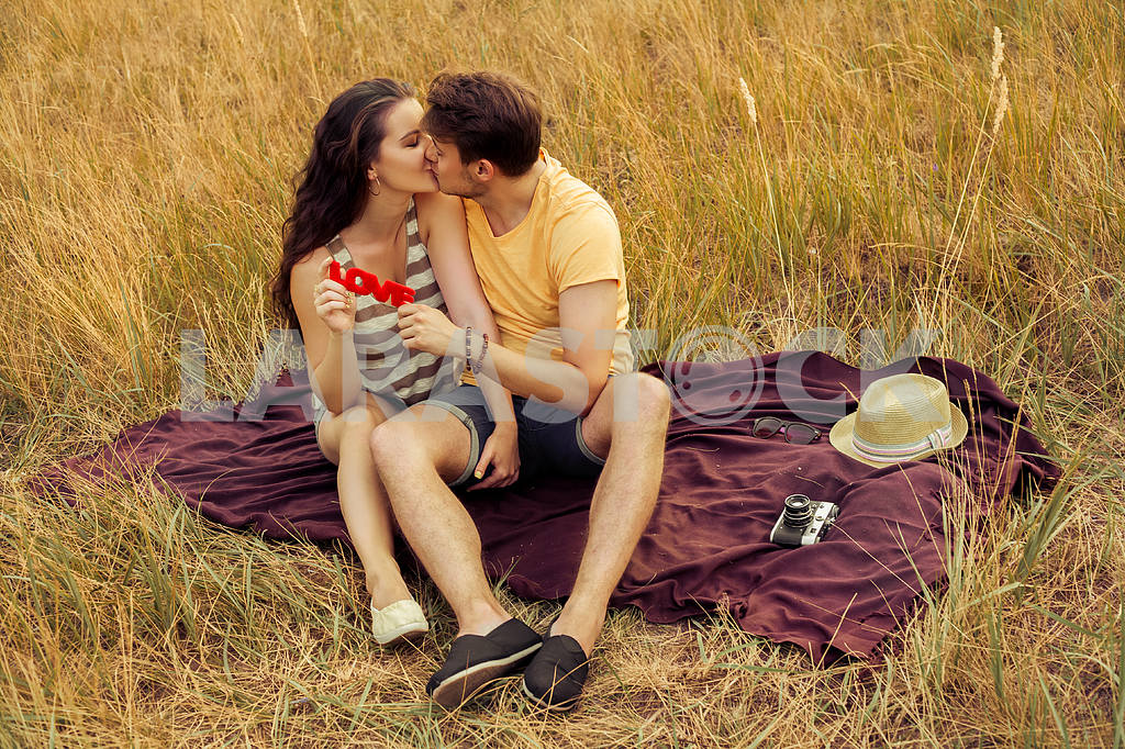 Young fashion beautiful loving casual style couple  lying down on floral field in autumnal park, warm sunny day, enjoying family, romantic date, happiness and love concept. — Image 19872