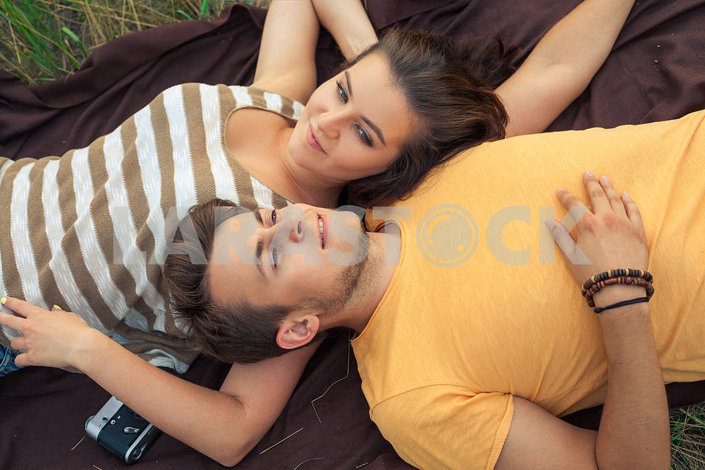 Young fashion beautiful loving casual style couple  lying down on floral field in autumnal park, warm sunny day, enjoying family, romantic date, happiness and love concept. — Image 19874