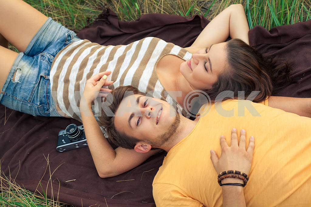 Young fashion beautiful loving casual style couple  lying down on floral field in autumnal park, warm sunny day, enjoying family, romantic date, happiness and love concept. — Image 19876