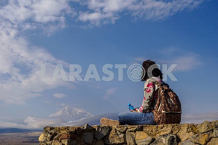 Man sitting on rocks and looking at Mount Ararat.