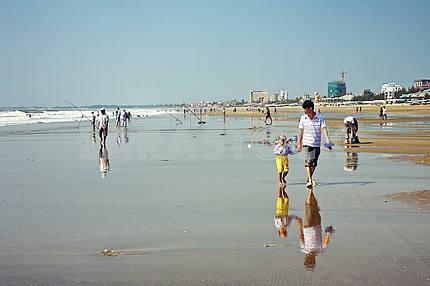 Папа с ребенком гуляет по пляжу