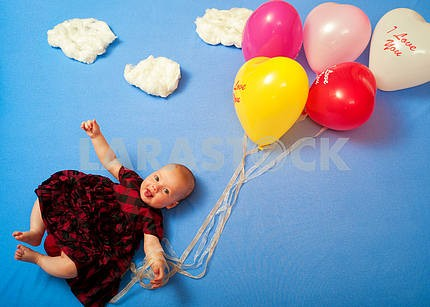 Baby is flying on balloons