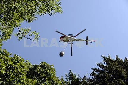 Вертолет несет груз в Альпах