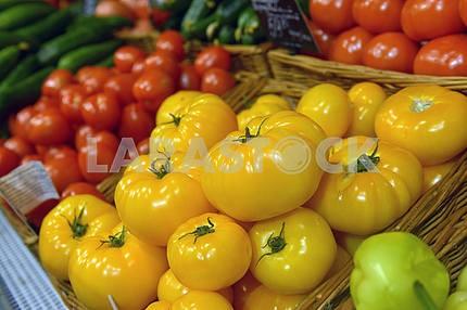 Желтые и красные помидоры на дисплее