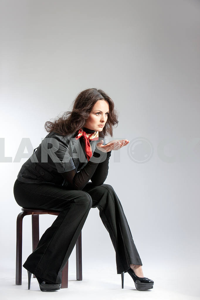 Woman in black suit sitting on a stool — Image 22560