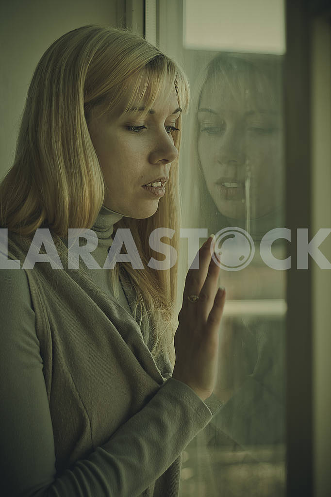 Young girl sitting by the window — Image 22798