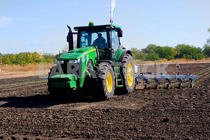 Green tractor handles field