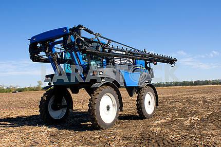 Большой синий трактор для опрыскивания химикатами