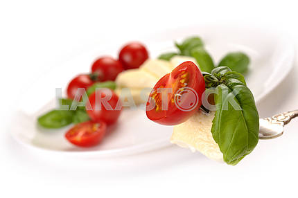 Mozzarella with tomato and basil on fork