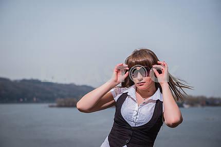 Женщины, занимающие солнцезащитные очки с светло-каштановые волосы, одетый в белый и черный, портрет, солнечный день, с видом на реку и город на заднем плане