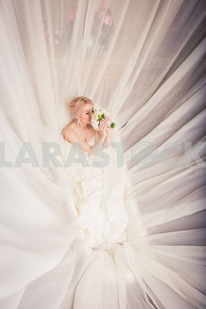 Blonde Bride in bathroom surrounded with the veil, felling the smell of bouquet — Image 28929
