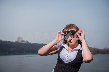 Девушка с Солнцезащитные очки Женщины занимают солнцезащитные очки со светло-коричневые волосы, одетый в белый и черный, портрет, солнечный день, с рекой и город на заднем плане