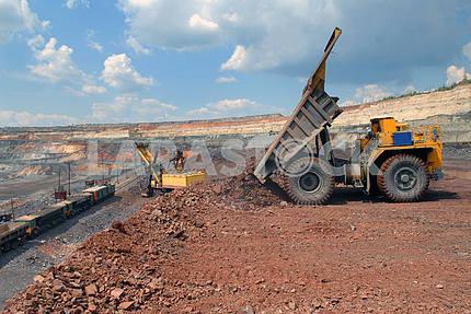 Dump-body truck unloading in mine