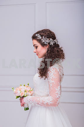 Brown-haired bride (women) with curly hair - rustic style - side view, with wedding bouquet in her hands, captured in studio