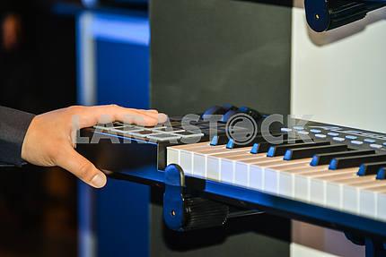 Рука на пульте многоголосного клавишного инструмента