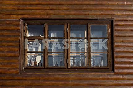 Деревянное окно деревянного дома декорировано бутылками