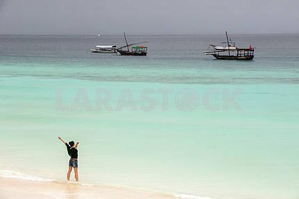 Zanzibar, girl at the sea during the rainy season