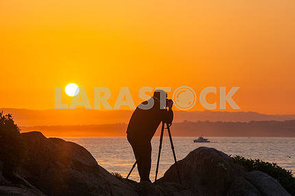 Photographer is macking a photo of sunrise  on the shore of the Pacific ocean