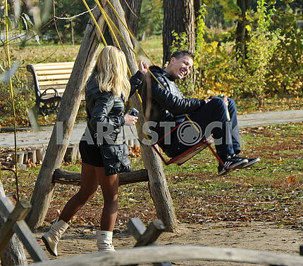 Boy and girl go for a drive on a swing in the park Kiev Feofania