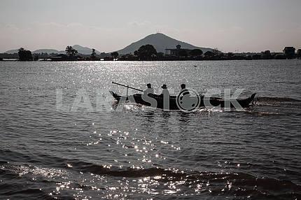 """Прогулочная Лодка в солнечных искрах на озере Тонлесап с пасажирами, что едут """"охотиться"""" на туристов"""