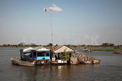 Домик, построенный на баркасе, на воде озера с высоко поднятой современной антенной