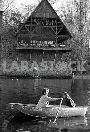 "Girls ride on a boat on Venetian canals in Kiev Hydropark in the background, ""Mlyn"" restaurant in 1990"