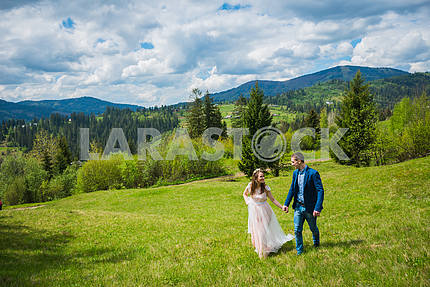 Wedding in mountains, a couple in love, mountains background, surrounded dandelions, among the lawn with the green grass,