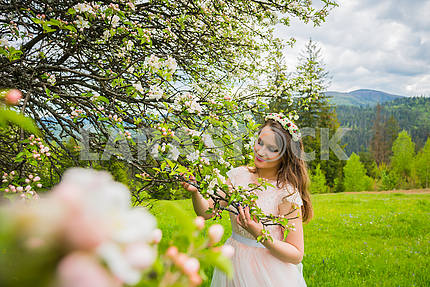 Bride standing near the blooming apple tree,