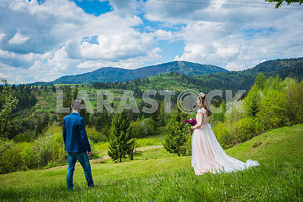 Bride and groom having a romantic moment on their wedding day looking forward, mountains and blue cloudy sky