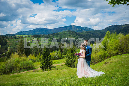 Beautiful young wedding couple holding each other with hands,