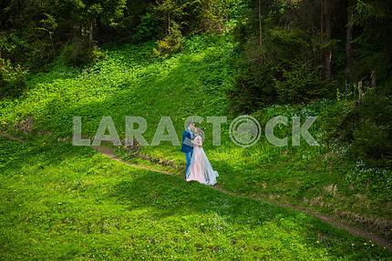 Wedding in mountains, a couple in love, mountains background, standing surrounded forrest, among the lawn with the green grass,