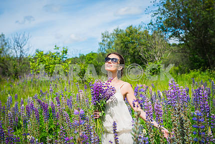 Young woman, happy, standing among the field of violet lupines, smiling, purple flowers. Blue sky on the background. Summer, with bouquet, in sunglasses looking in the sky, dreaming