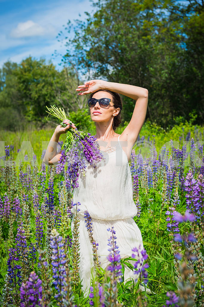 Young woman, happy, standing among the field of violet lupines, smiling, purple flowers. Blue sky on the background. Summer, with bouquet, in sunglasses holding her hand near head — Image 34544