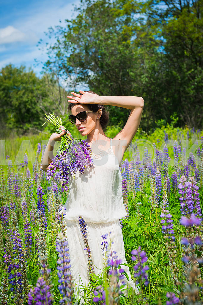 Young woman, happy, standing among the field of violet lupines, smiling, purple flowers. Blue sky on the background. Summer, with bouquet, in sunglasses holding her hand near head — Image 34545