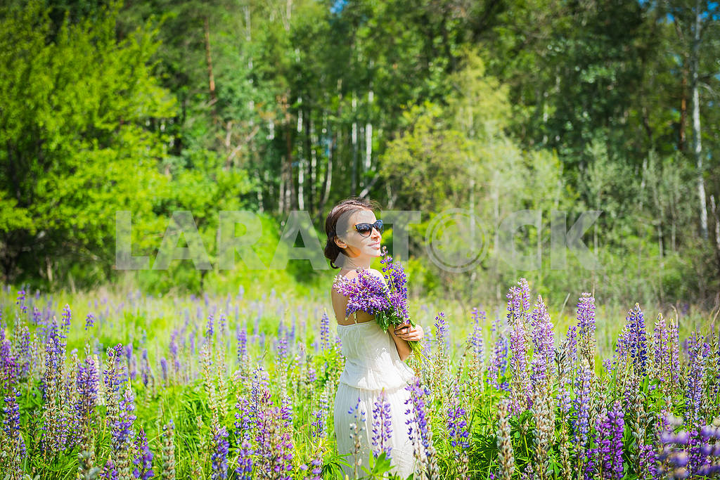 Young woman, happy, standing among the field of violet lupines, smiling, purple flowers. Blue sky on the background. — Image 34547