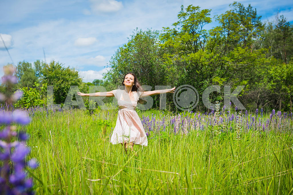 Young woman, happy, standing among the field of violet lupines, smiling, — Image 34549
